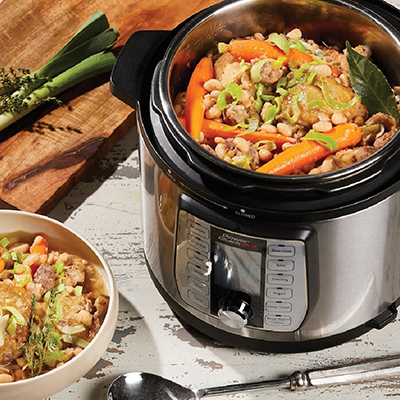 A stew with carrots and beans inside a pressure cooker.