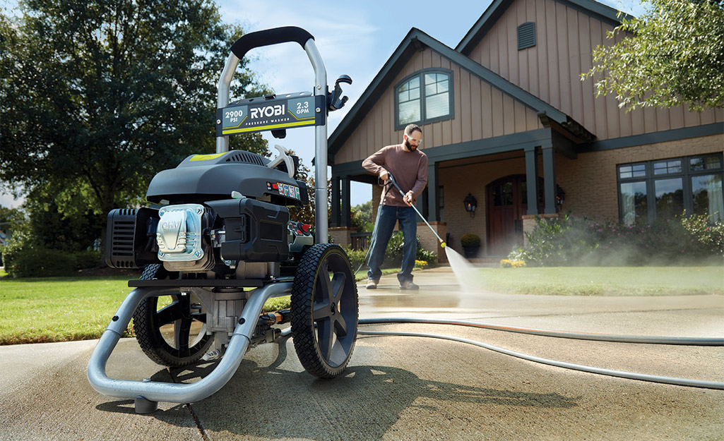 A man uses a gas powered washer to clean his sidewalks.