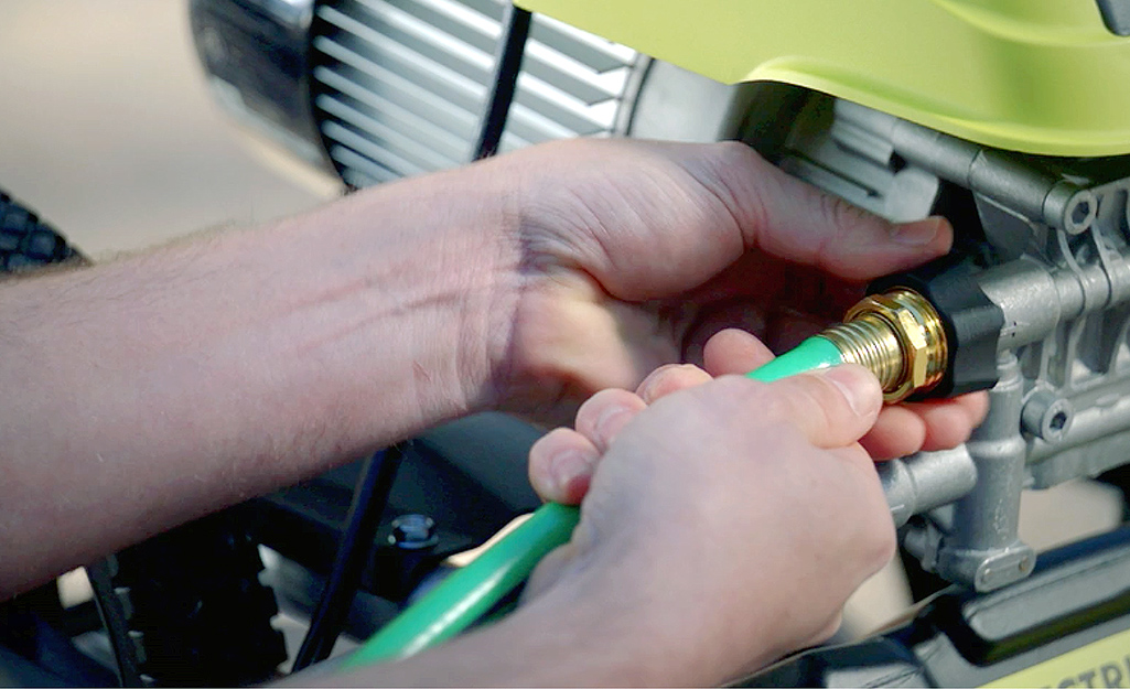 A person attaches a garden hose to the water inlet on their pressure washer.