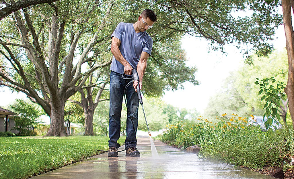A man wears safety goggles to pressure wash his sidewalk.
