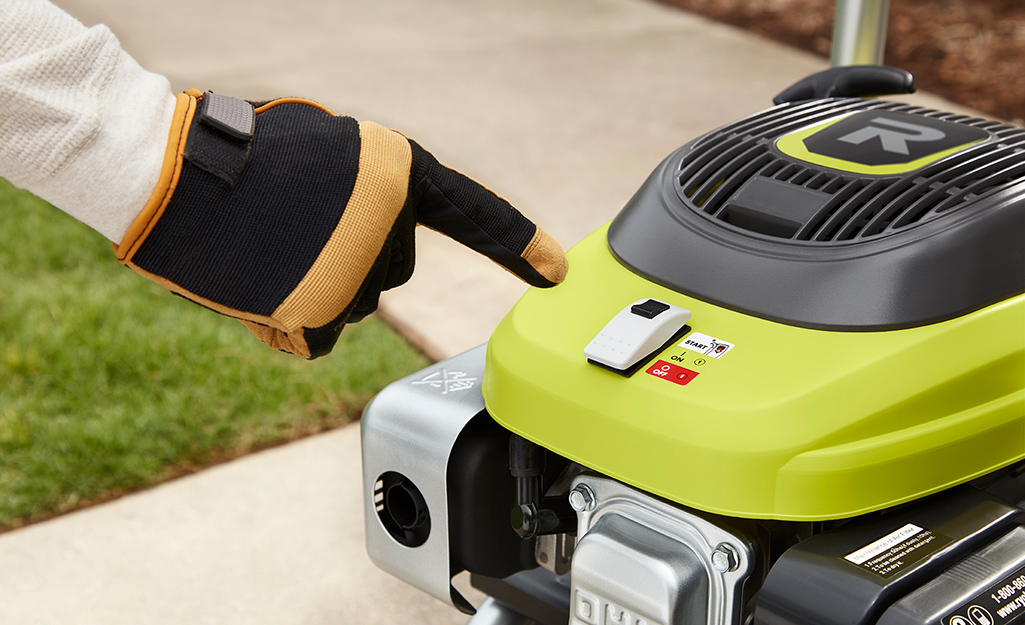 A person wearing work gloves turns off a pressure washer.