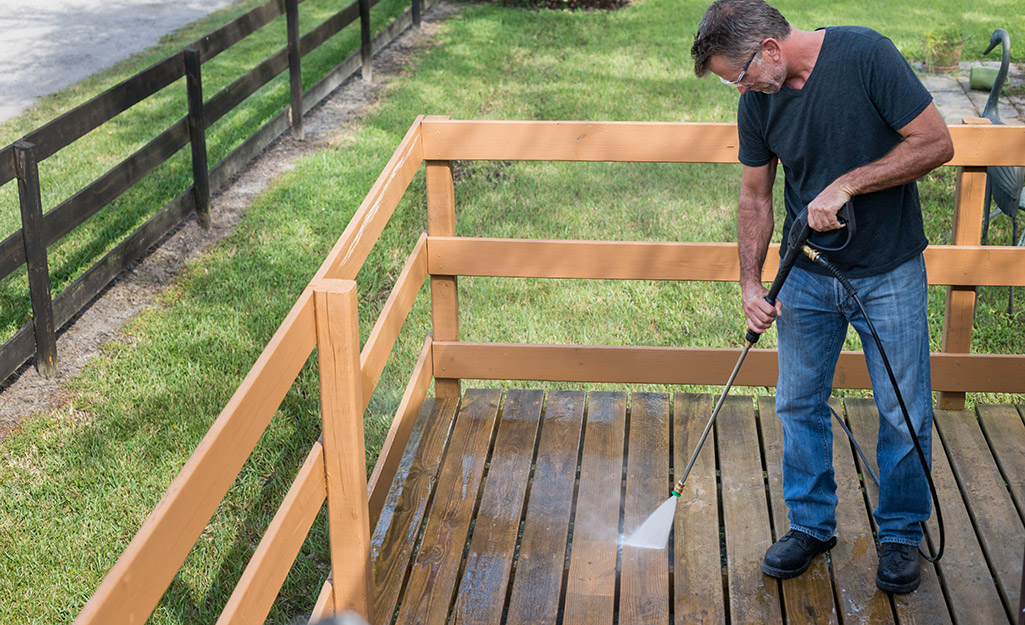 A man pressure washes his deck.