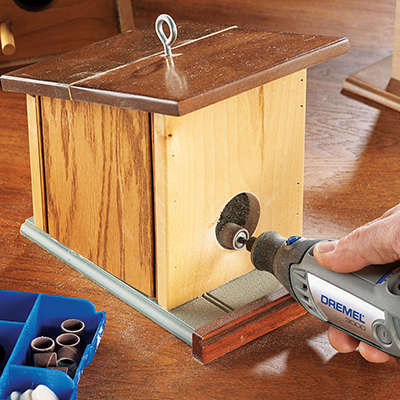 A rotary tool sands the entrance hole of a DIY wooden bird feeder.