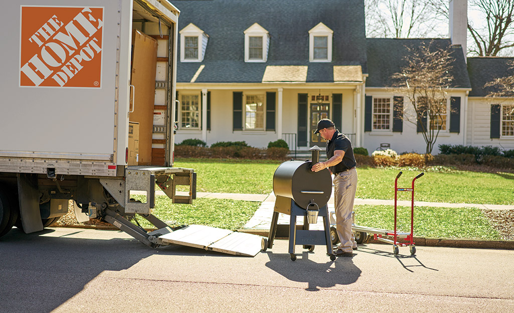 A Home Depot associate dropping off a package to a homeowner.