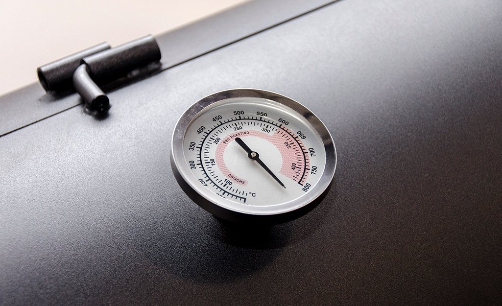 A thermometer on a grill.