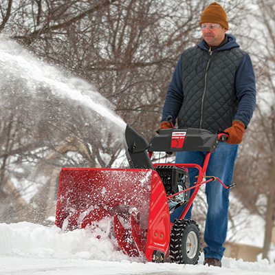 A person using a power snow blower to clear snow.