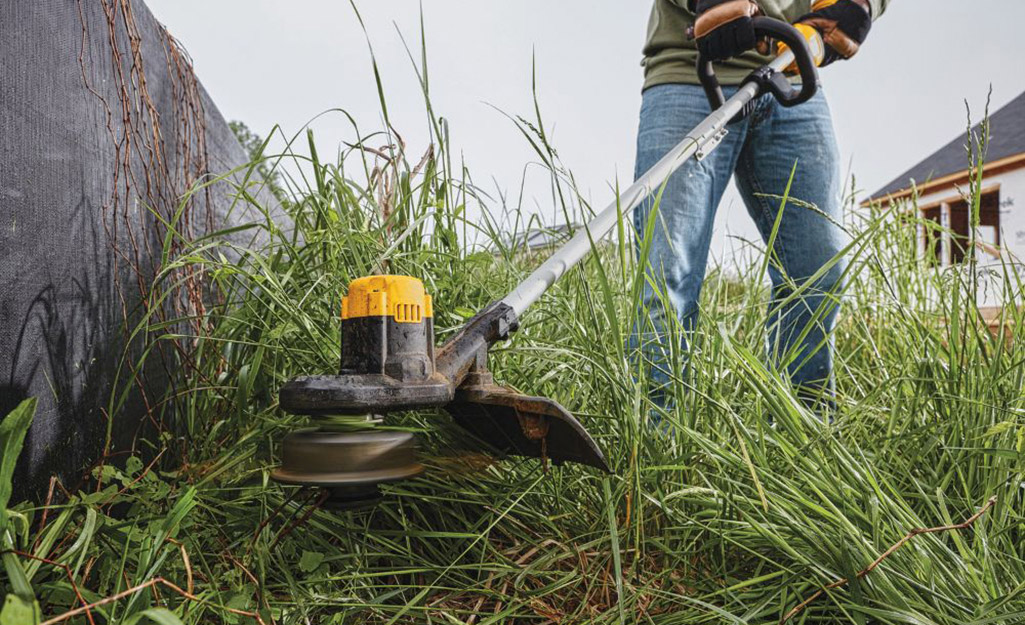 Close up of a person using a string trimmer.