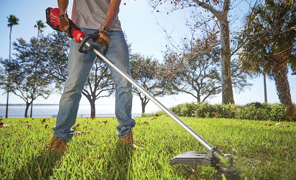 A man cuts grass using the string trimmer.