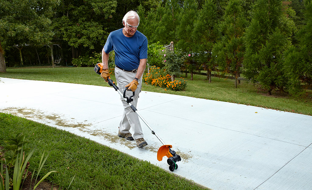 A man uses a string trimmer to edge the lawn by his driveway.