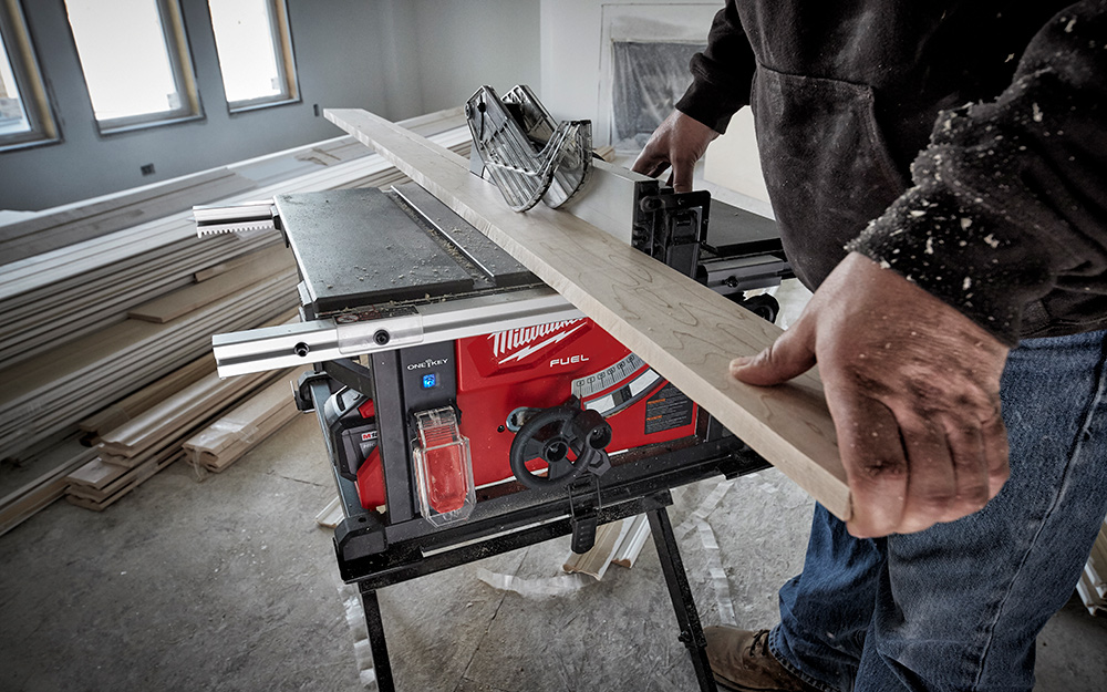 A person cutting wood with a table saw.