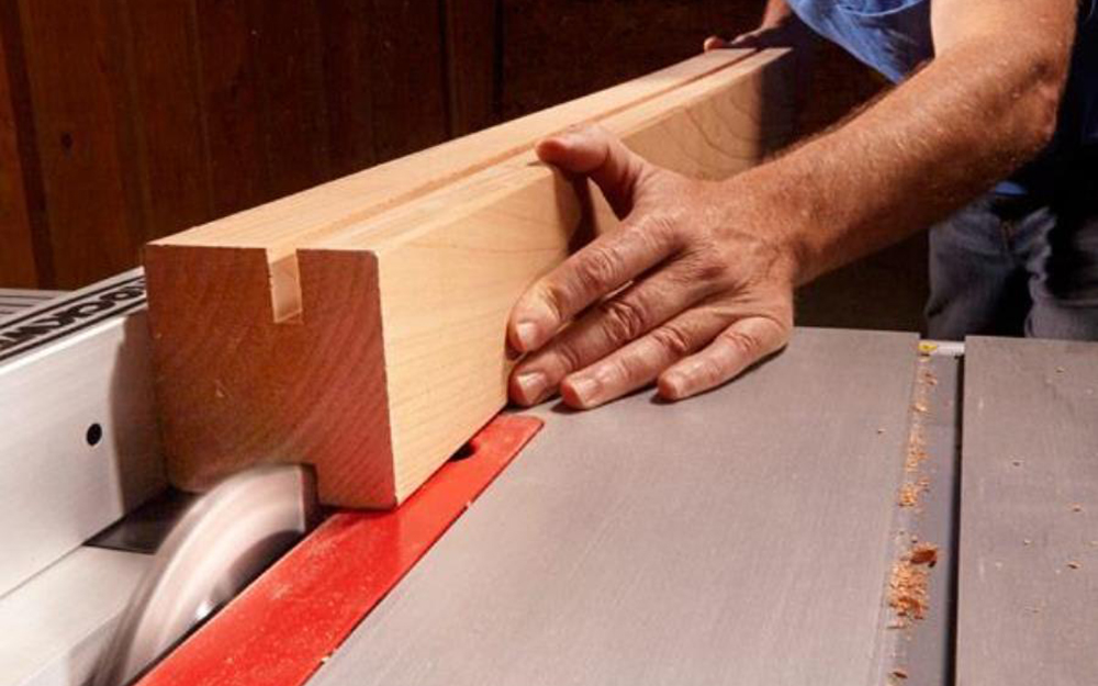 A person cutting a dado in a piece of wood.