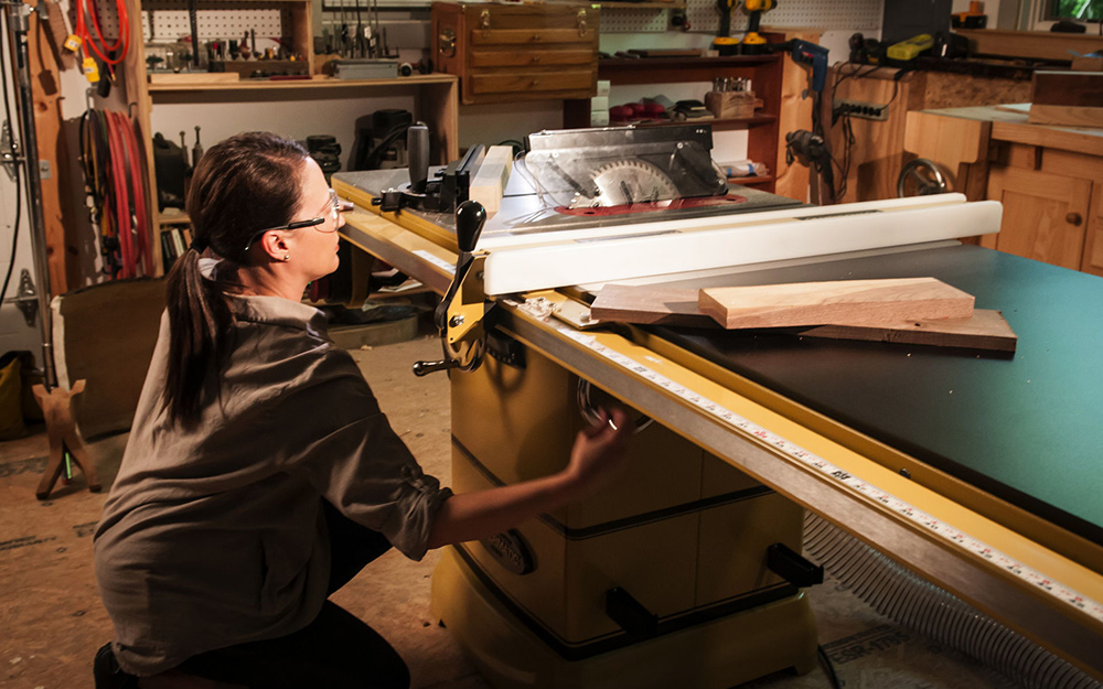 A person using a stationary table saw.