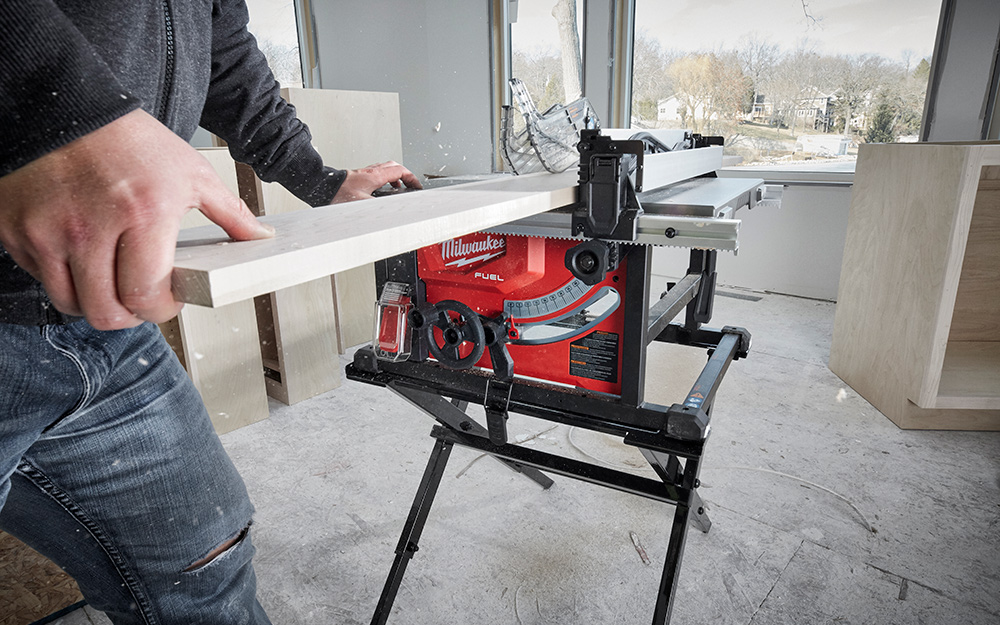 A man cutting wood with a table saw.