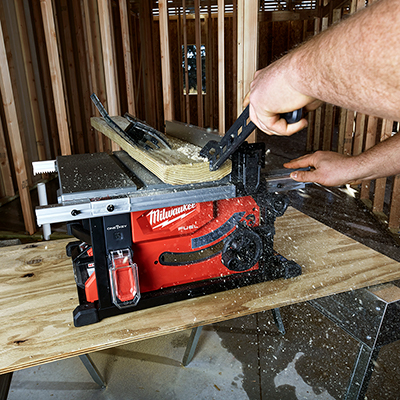 Man using a table saw to cut wood