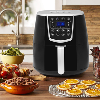 An air fryer on a countertop with various prepared foods on display.