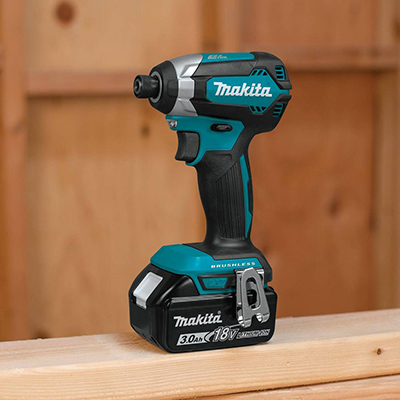 A cordless impact driver resting on a board.