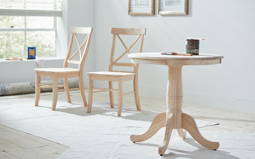 Hai cái ghế không sơn và một cái bàn đứng trên vải thả,