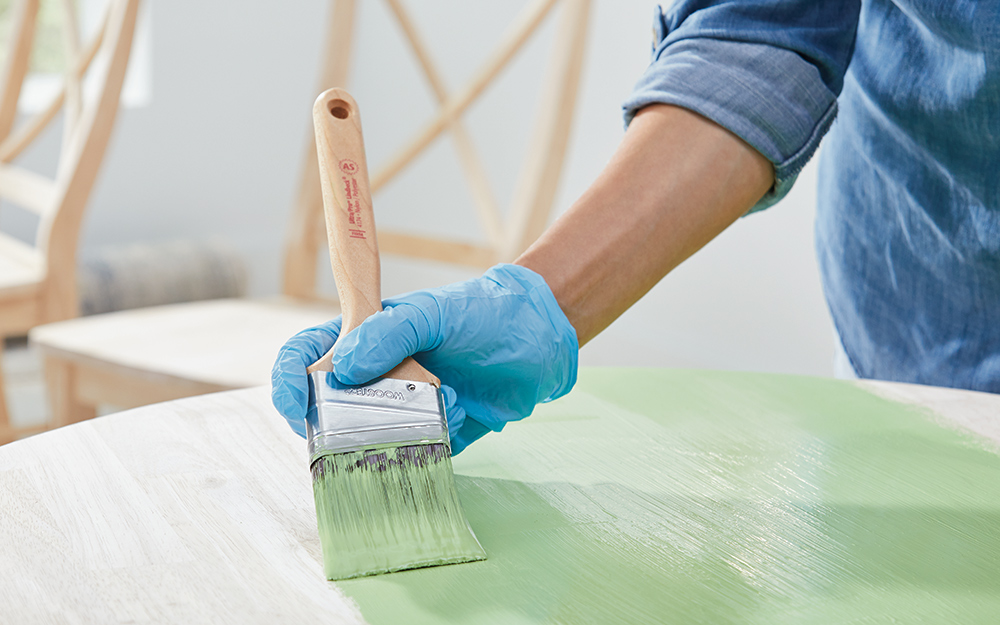 A person uses a brush to apply green chalk paint to a table.
