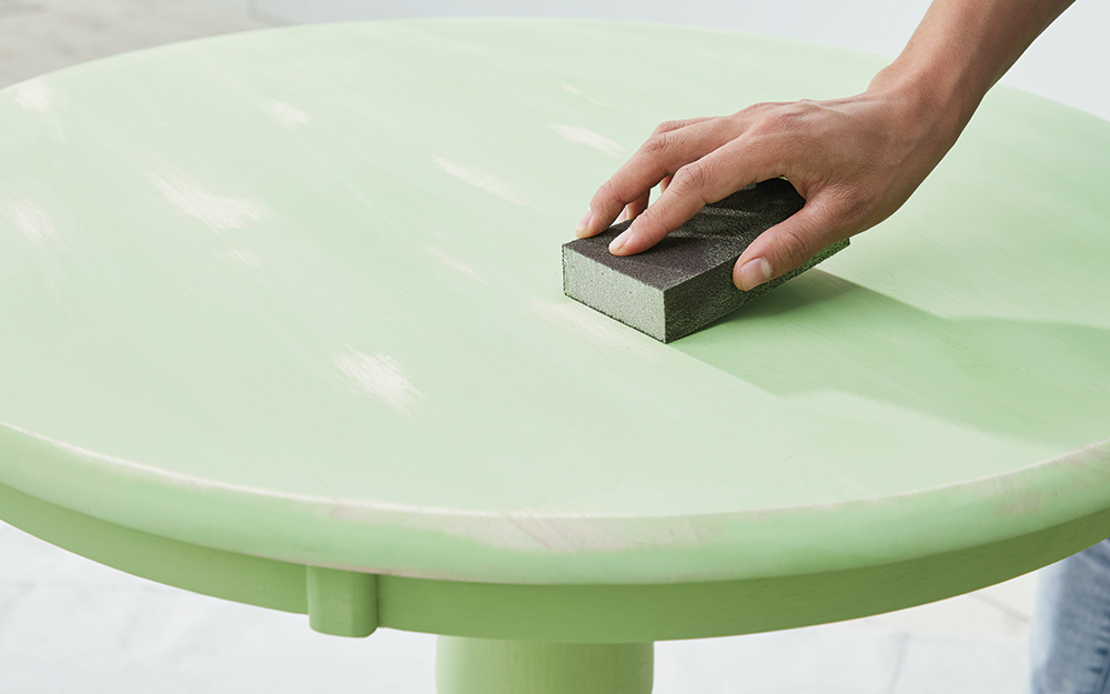 A person applies a sanding block to a table painted with green chalk paint.