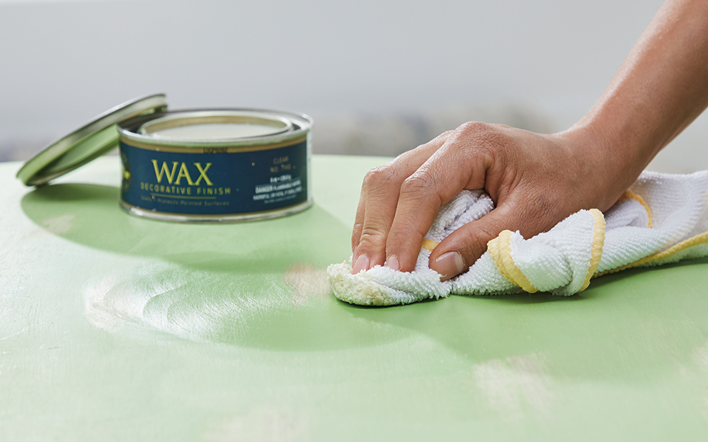 A person applies furniture wax to a table painted with chalk paint.