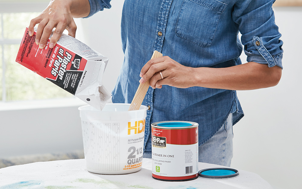 A person mixes plaster of Paris and latex paint.