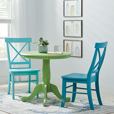 A green table and two blue chairs painted with chalk paint in a white room.