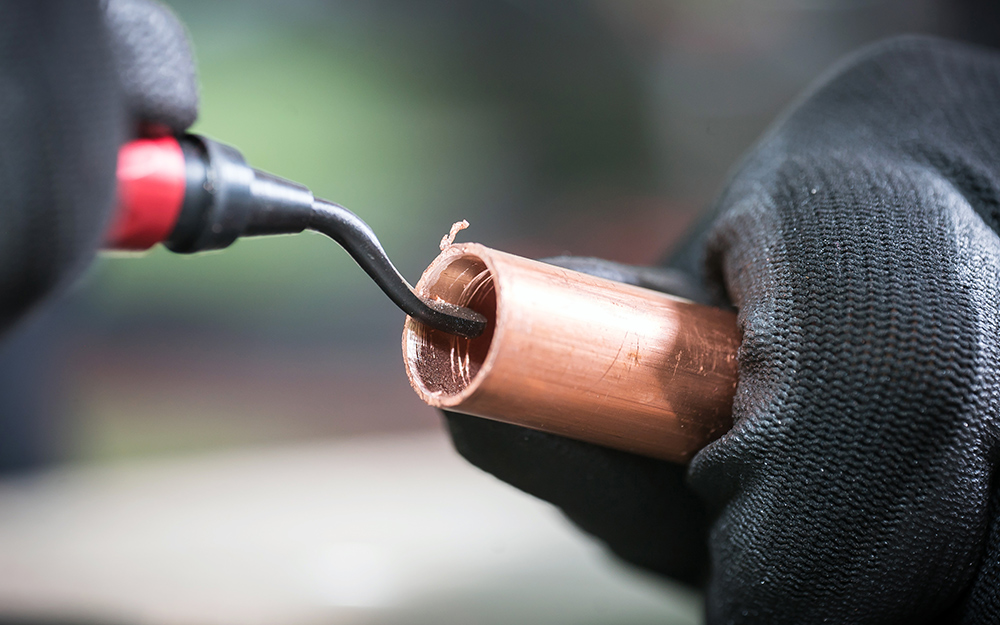 A person cleans the end of copper tubing with a deburring tool.
