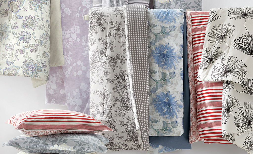 Several types of comforters in different patterns and colors.