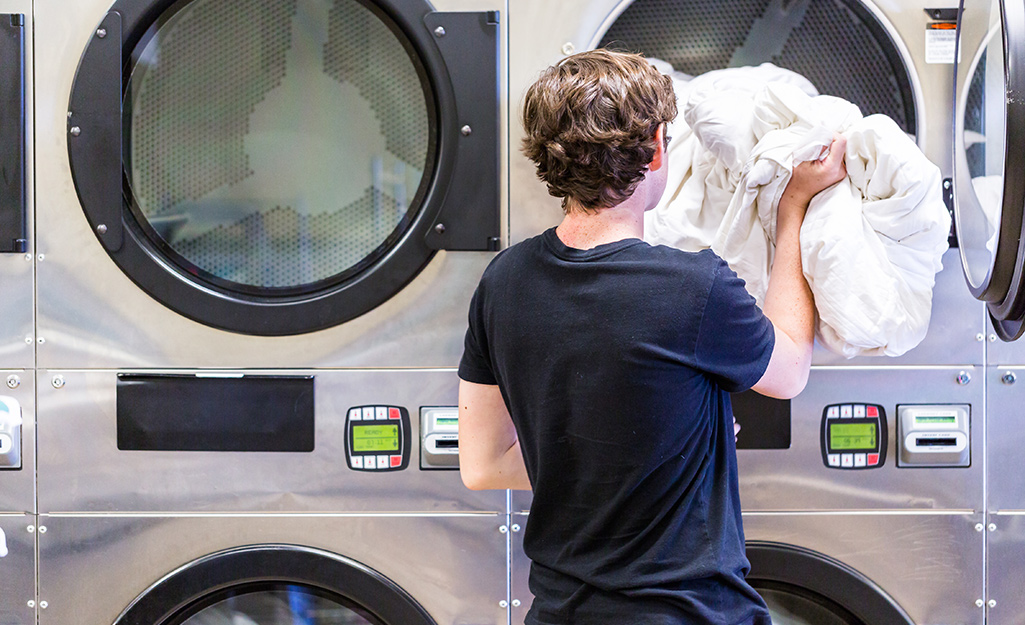 A person putting a comforter in a washing machine.