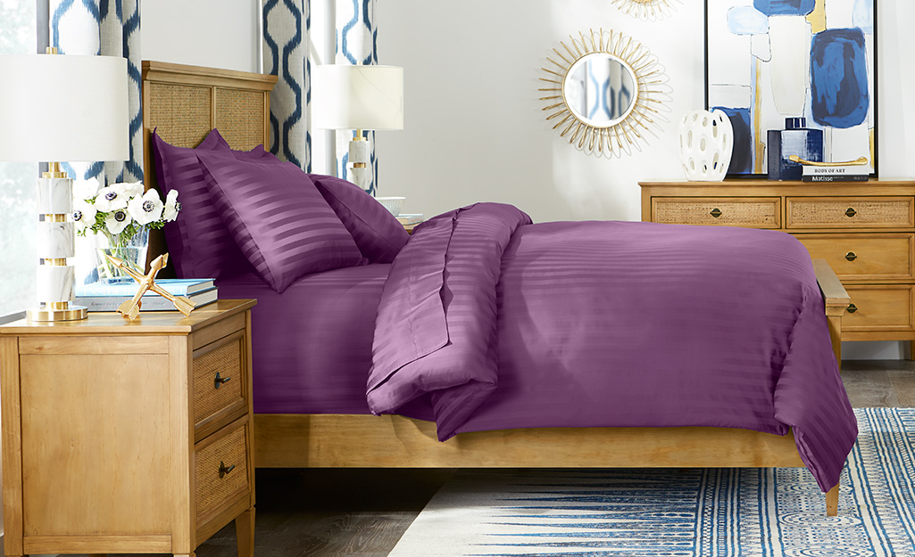A purple comforter on a bed.