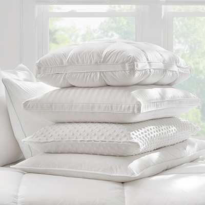 A stack of clean, white pillows on a bed.