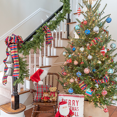 A decorated Christmas tree in a corner near a stairway.