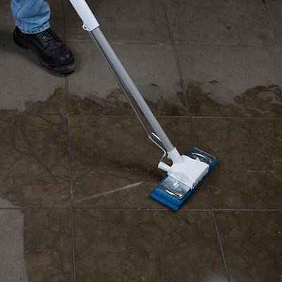 Person mops a waterproofed tile floor.