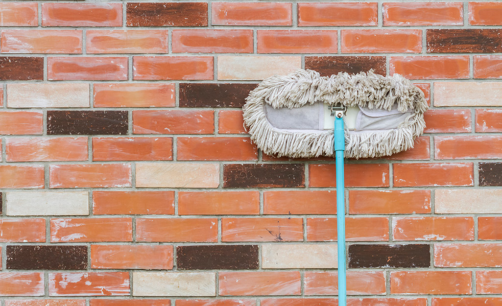 A person uses a mop to clean dirt off a brick surface.