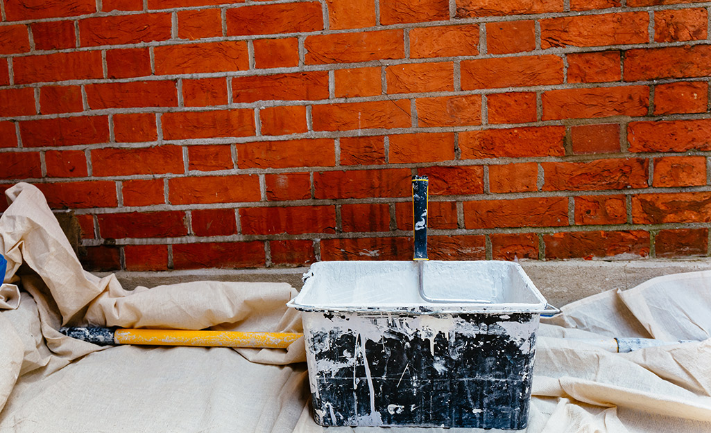 Drop cloths cover the floor around a brick wall for protection before whitewashing.