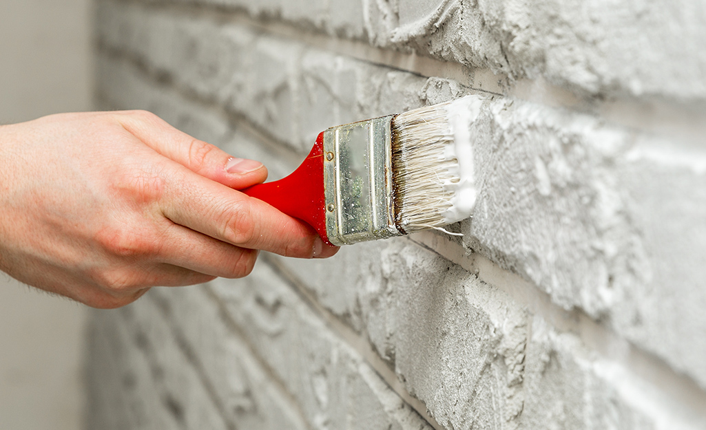 A person uses a brush to apply whitewash to a brick wall.