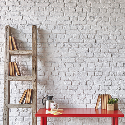 A bookcase and a small red table lean against a wall of whitewashed brick.