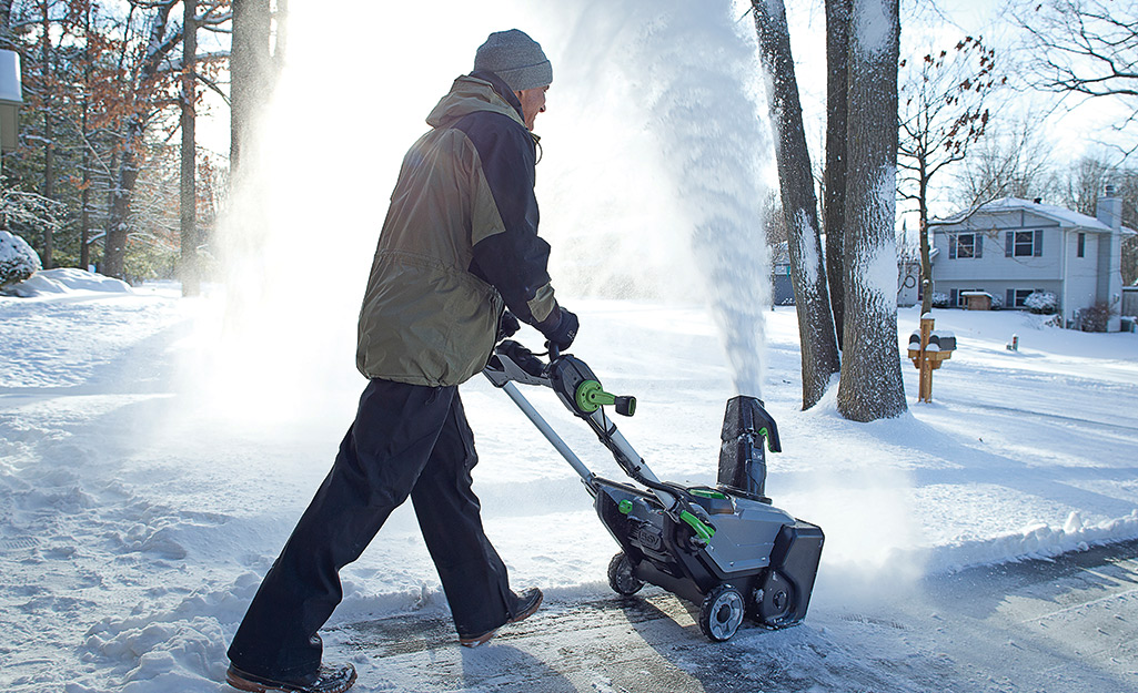 Person using a snow blower to remove snow.