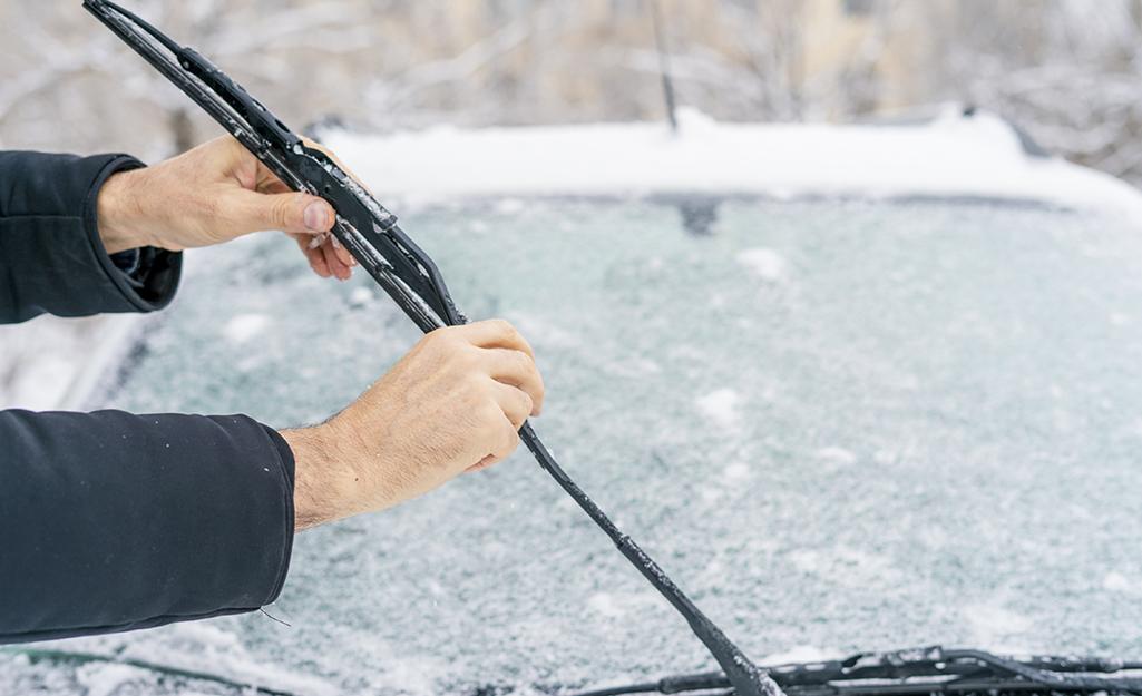 Một người giơ cần gạt nước của một chiếc ô tô phủ đầy tuyết.