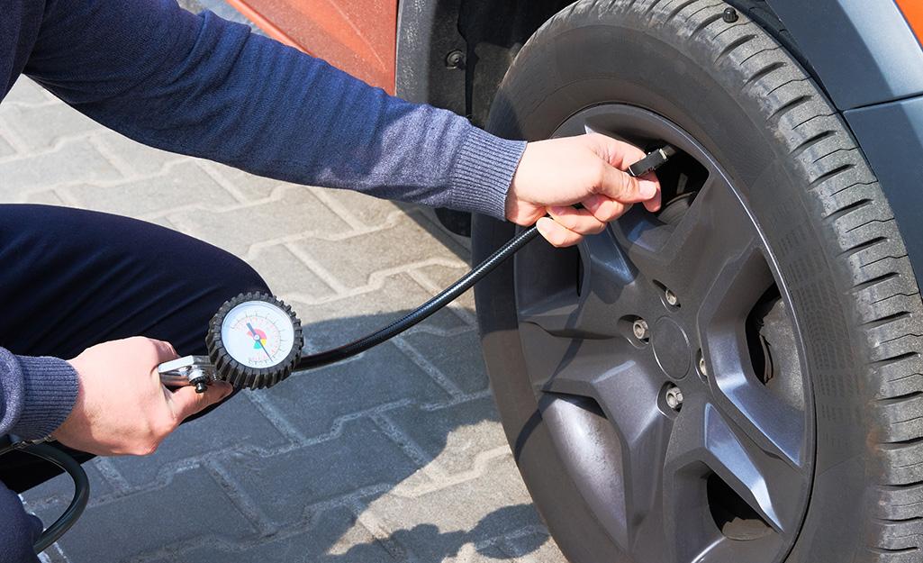 Một người sử dụng máy nén khí để bơm lốp ô tô.
