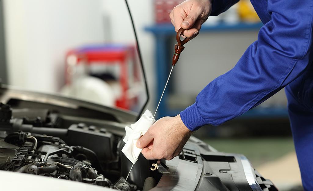 Một người kiểm tra và lau que thăm dầu động cơ của xe.