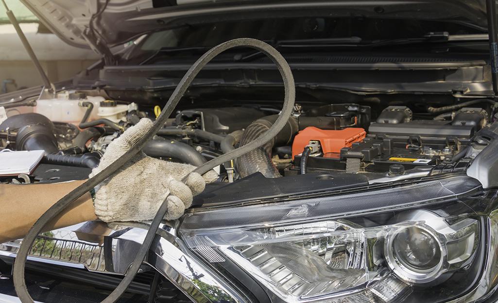Một người cầm dây đai động cơ của xe.