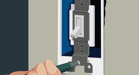 A person using a screwdriver to remove mounting screws from an light switch