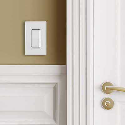 A white 3-way light switch next to a white door