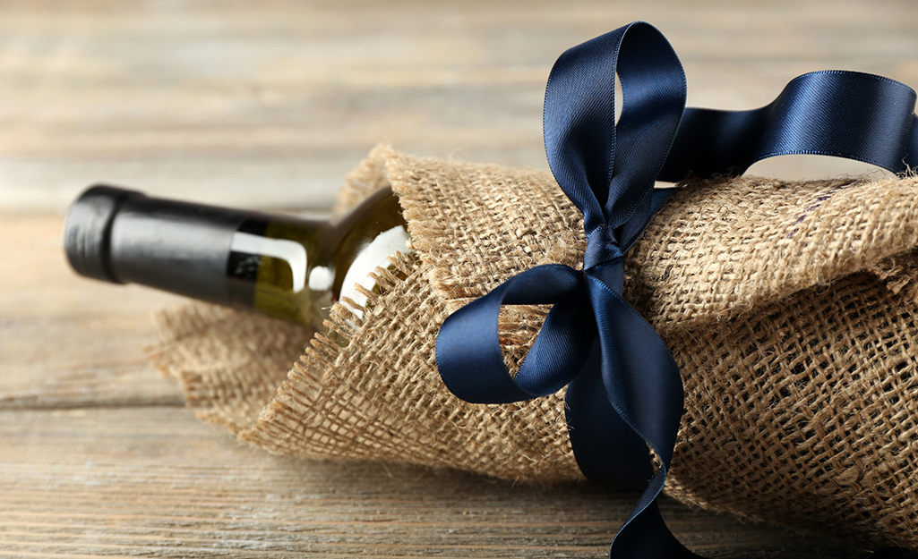 A wine bottle wrapped with burlap and tied with a ribbon.