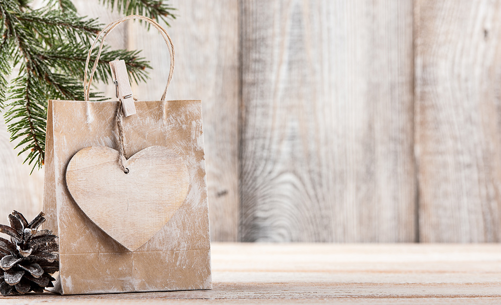 A brown gift bag with a paper heart tied to the bag handle.