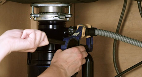 person-uses-wrench-on-garbage-disposal
