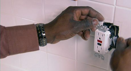 a person removes the old power outlet