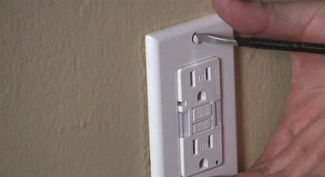 A person screws a wall plate over the new outlet.