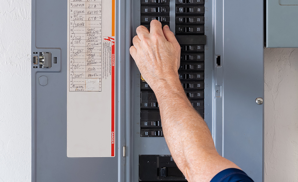 A person turning a circuit breaker off at the breaker panel.